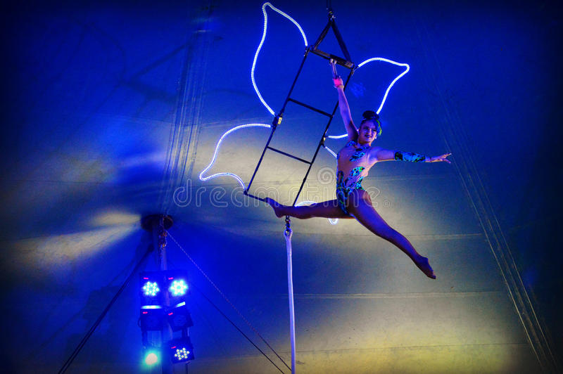Flying Trapeze Woman. A flying trapeze circus perfomer hanging on to a butterfly that is lit up with neon lights under the big top at Circus World Museum in stock images