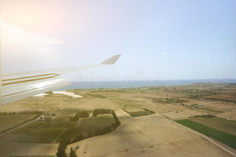 Flying and traveling, view from airplane window to land with fields stock photography