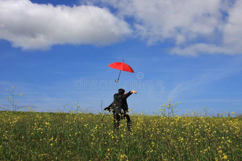 Flying umbrella. A young business man running after a flying umbrella stock images