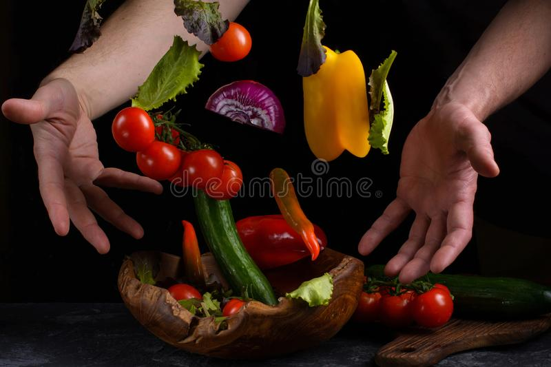 Flying vegetables for salad between male hands. Healthy vegetarian food is levitation over a wooden bowl on a dark stone table royalty free stock photo