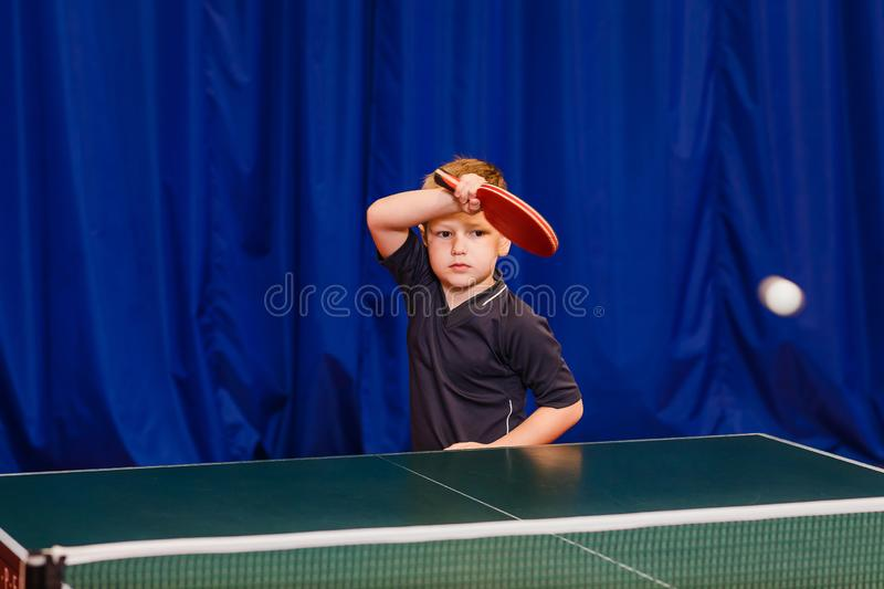 Flying white ball in table tennis,a child plays table tennis stock images