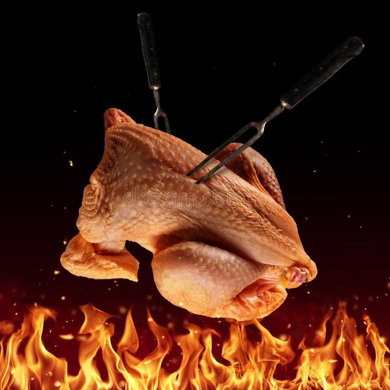 Flying whole raw chicken above grill flames royalty free stock photo