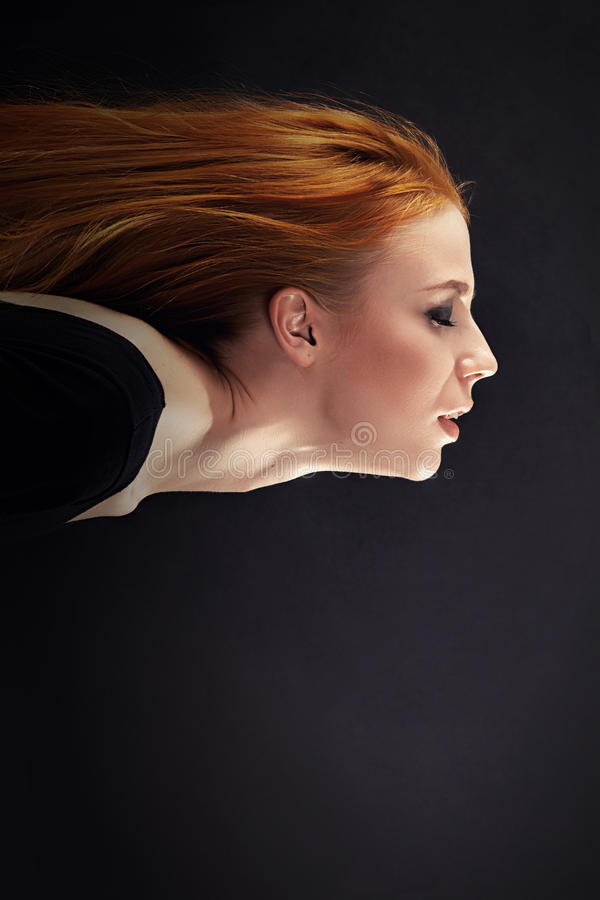 Flying woman profile. Profile of flying woman on black background with copyspace royalty free stock photo