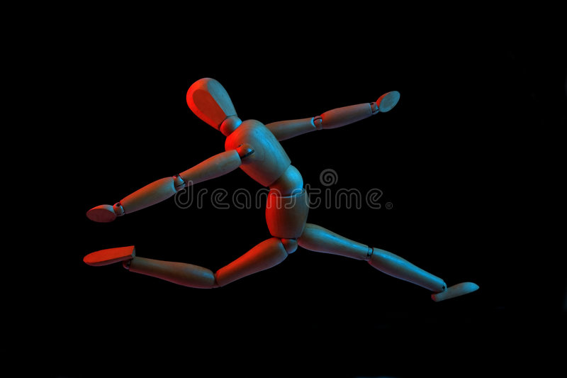 Flying wooden puppet. Isolated on black background, red and blue light stock photo
