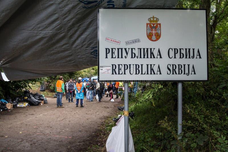 Flyktingar som samlar behing gränstecknet på Serbien Kroatiengräns i Berkasovo Bapska, på den Balkans rutten, under flyktingkris royaltyfri fotografi