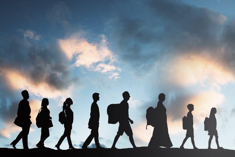 Flyktingfolk med bagage som i rad går arkivbild