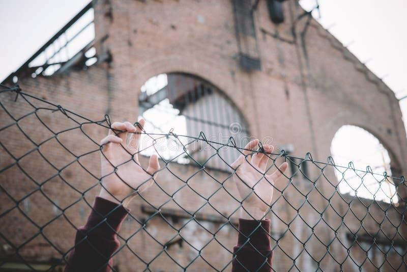 Flyktinghänder som håller metallstaketingreppet arkivfoton