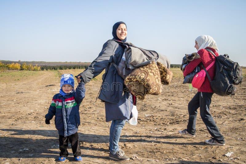 Flyktingkvinna som omges av barn som går till den KroatienSerbien gränsen, mellan städerna av Bapska och Berkasovo royaltyfria foton