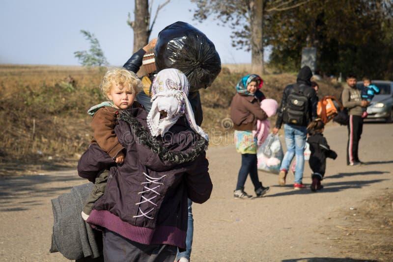 Flyktingkvinna som omges av barn som går till den KroatienSerbien gränsen, mellan städerna av Bapska och Berkasovo royaltyfri bild