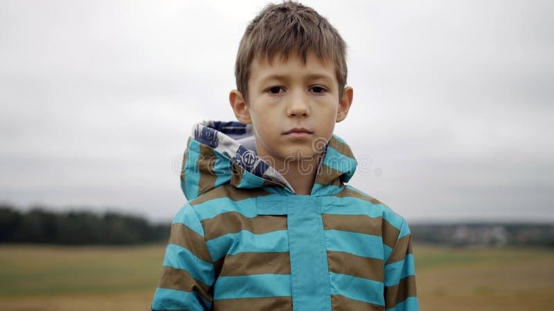 Flyktingpojken ser Compassionately på kameran, hemlös pojke, smärtar på framsida royaltyfria foton