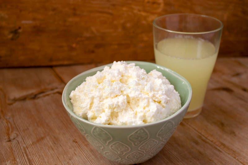 Flytande mjölka vassla i ett exponeringsglas och en keso i bunke på lantlig träbakgrund Mejeriproduktion arkivfoton