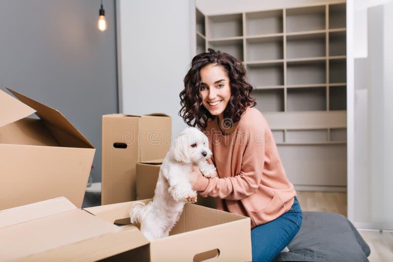 Flytta sig till den nya moderna lägenheten av den glade unga kvinnan som lite finner den vita hunden i lådaask Le till kameran av arkivbild