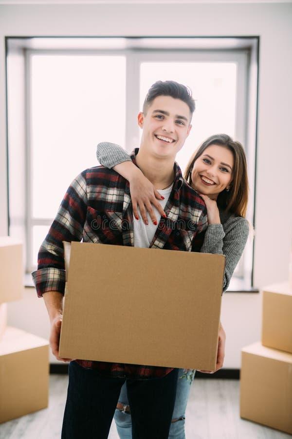 Flytta sig till ett nytt liv Parinnehavet boxas för att flytta händerna och att le på kameran förälskat anseende för par på fönst royaltyfria foton