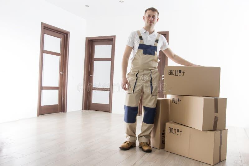 Flyttkarl med kartonger i ny lägenhet Förflyttning servar arbetaren i inomhus hus Laddare i likformig med asken arkivbild