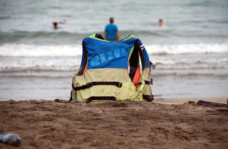 Flytväst på stranden royaltyfri foto