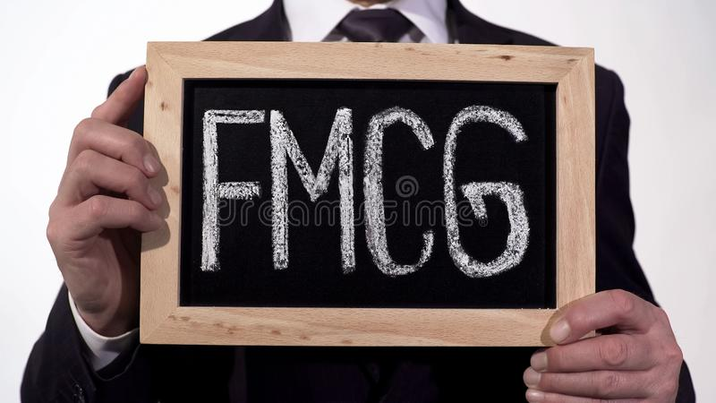 FMCG written on blackboard in businessman hands, consumer goods, retail trade. Stock footage royalty free stock photo