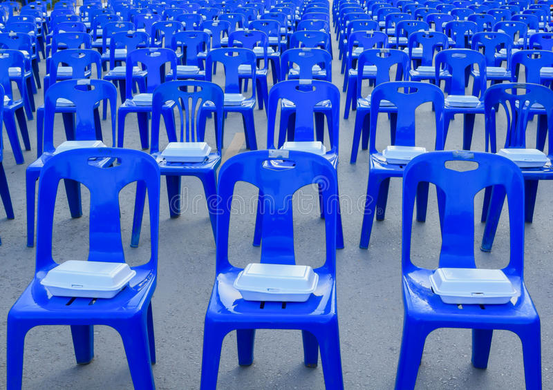 Foam box on blue plastic chairs. Pattern of white foam box on blue plastic chairs stock photos