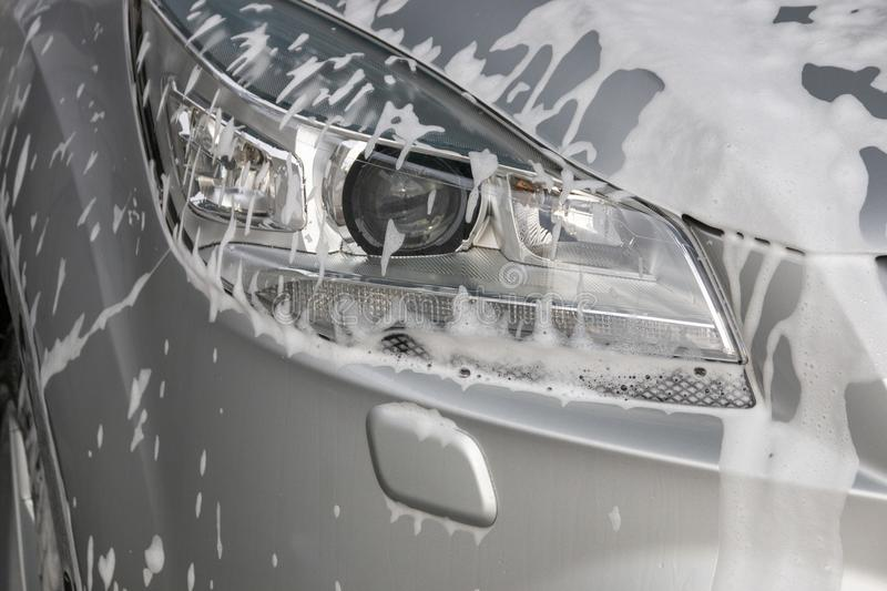 Foam On A Car Light. A Close up of soap foam on the left side of the main light of a sliver car stock photography