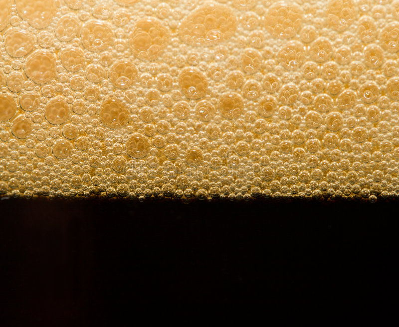 Foam from dark beer with bubbles stock photography