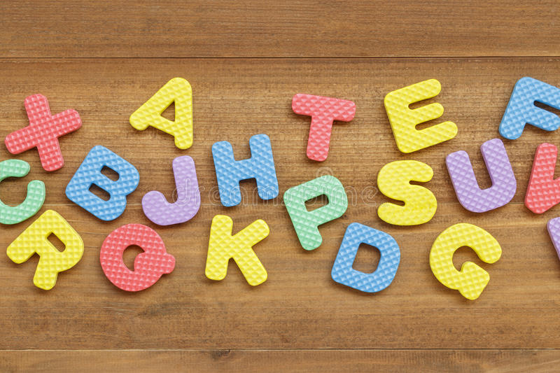 Foam english alphabet letters on wooden background royalty free stock image