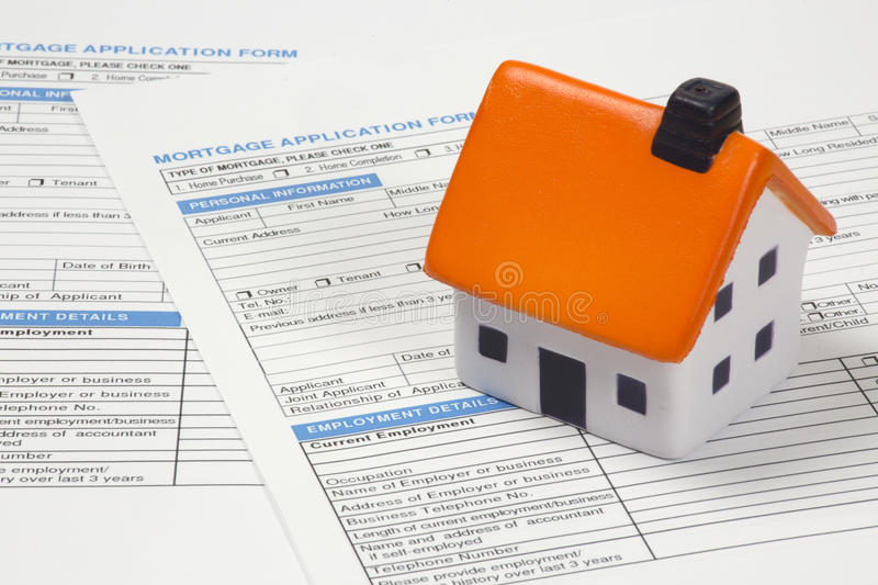 Foam house on top of mortgage papers. Mortgage documents with stress ball house stock image