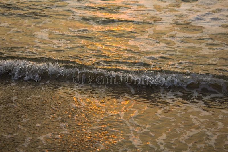 Foam of sea waves close-up with highlights of the evening sun. A foam of sea waves close-up with highlights of the evening sun stock image