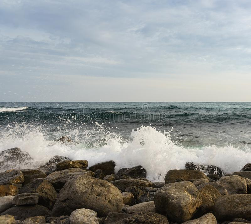Foam waves break on large rocks on the shore. Evening. Light stock photography