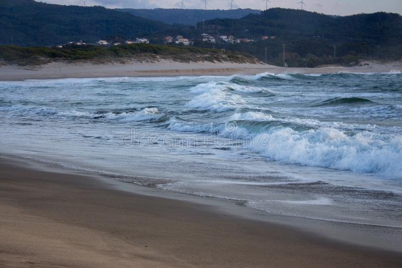 Foaming ocean waves breaking on sandy shore in evening dusk. Surf on beach with village and hills on background. royalty free stock image