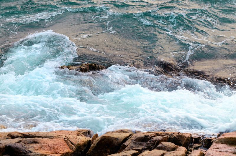 Foaming sea water hits stone beach, wave and beach, nature background concept. Photo with motion blur stock photos