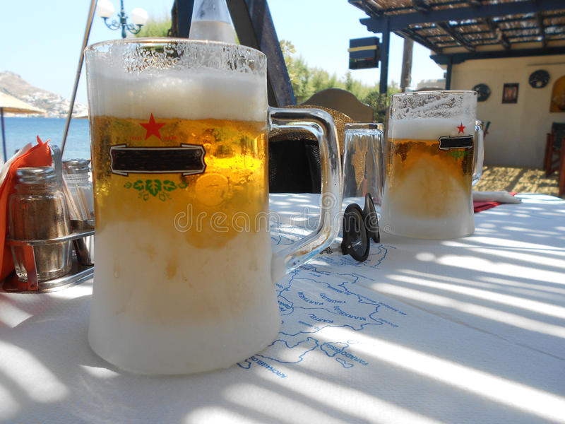 Foamy beer in greece. Best friend, a cold beer in hot weather stock photography