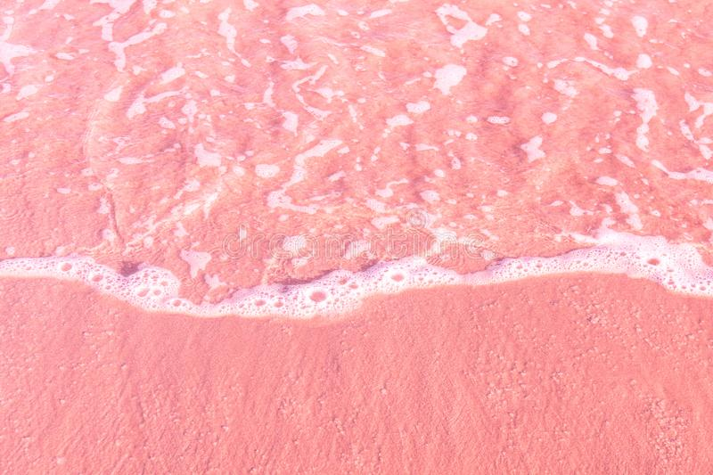 Foamy clear sea wave rolling to pink sand shore beach. Aerial view from above. Beautiful tranquil idyllic scenery. Tropical nature royalty free stock photos