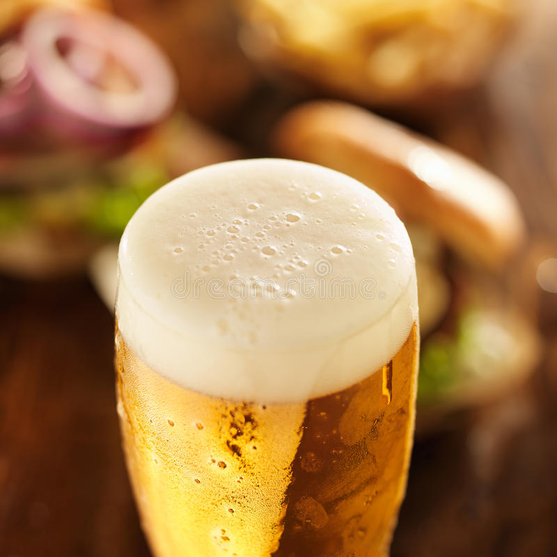 Foamy cold glass of beer. With burgers in background royalty free stock photo