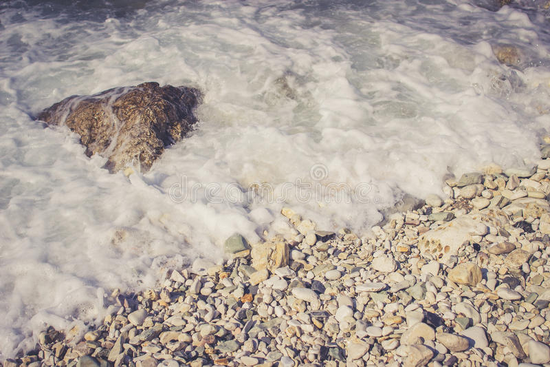 Foamy fala uderza otoczak skały na plaży obrazy royalty free