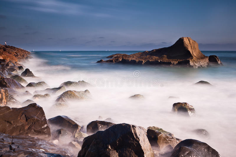 Foamy Pacific. Long exposure seascape with foamy waves splashing against a rocky Californian shore stock photos