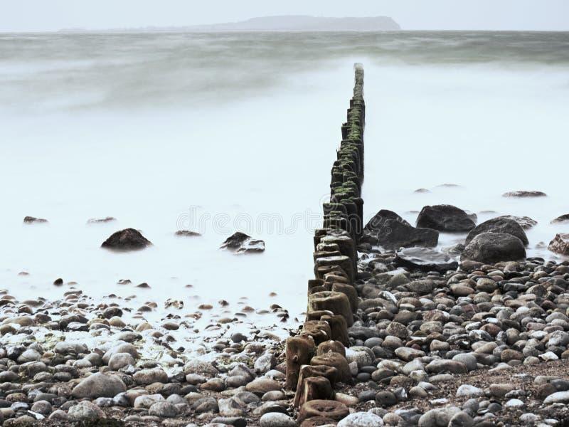 Foamy pozioma wodego donne dużymi falami uderza w starych falochronów słupy w morzu bałtyckim obraz stock