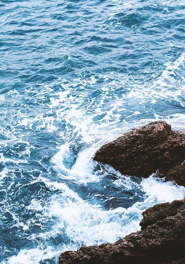 Foamy sea water. Sea water with foam. Foamy sea water flows through the stones royalty free stock photography