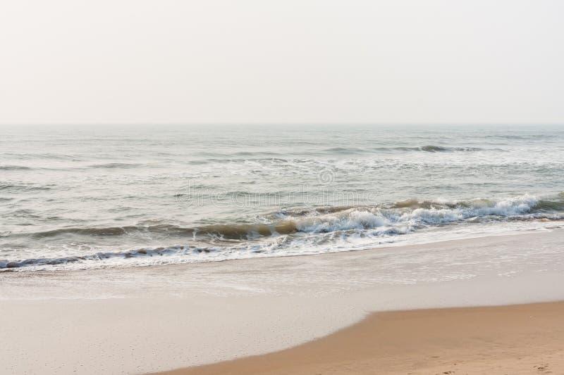 Foamy waves on calm beach stock photos