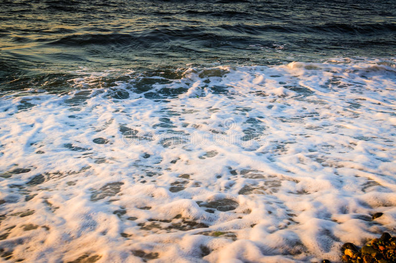 Foamy Shore. Light of the setting sun hitting to the foamy waves of the sea and creates shimmering reflections on its surface stock photo