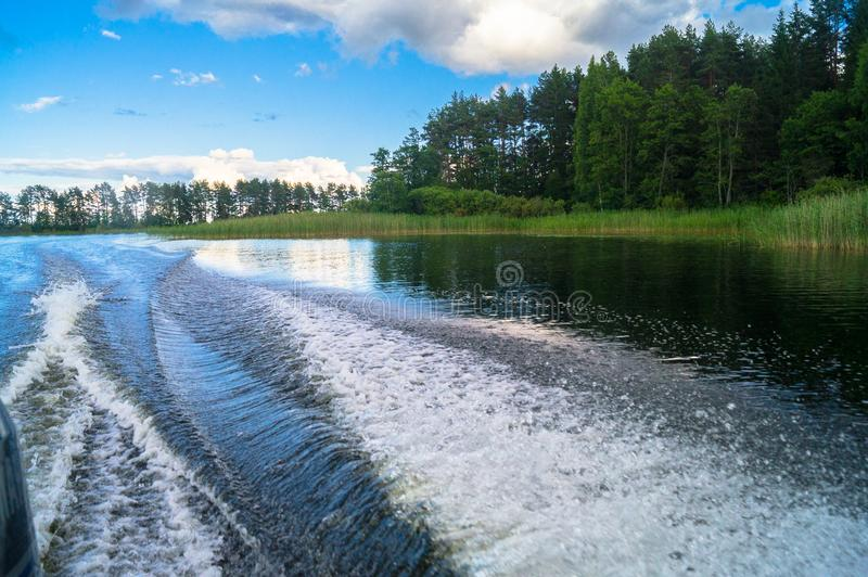 Foamy trail on the water surface behind the fast moving motorboat. The lake Seliger, Russia. royalty free stock photos