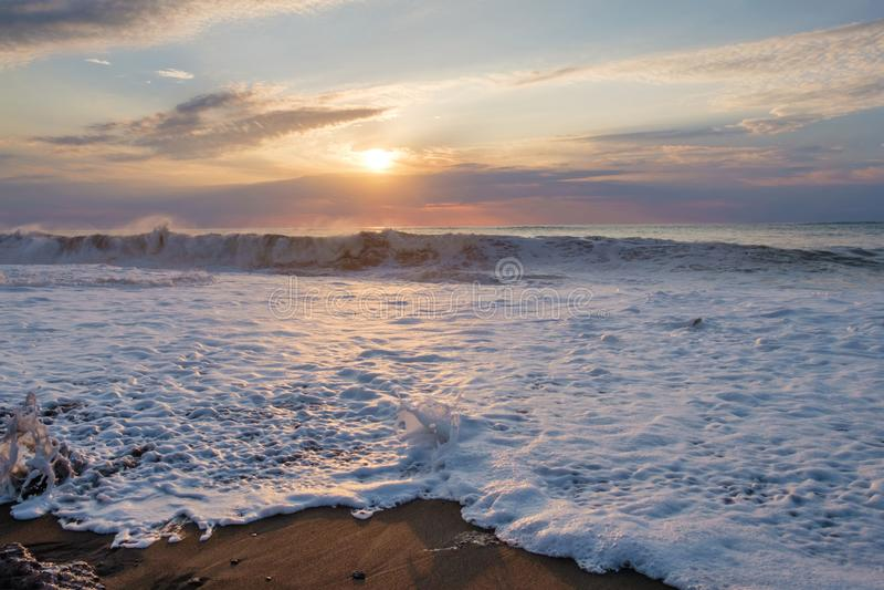 Foamy wave. At the sunset sandy beach stock photo