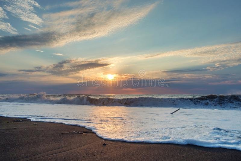 Foamy wave. At the sunset sandy beach royalty free stock image