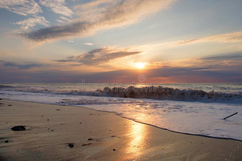 Foamy wave. At the sunset sandy beach royalty free stock photo