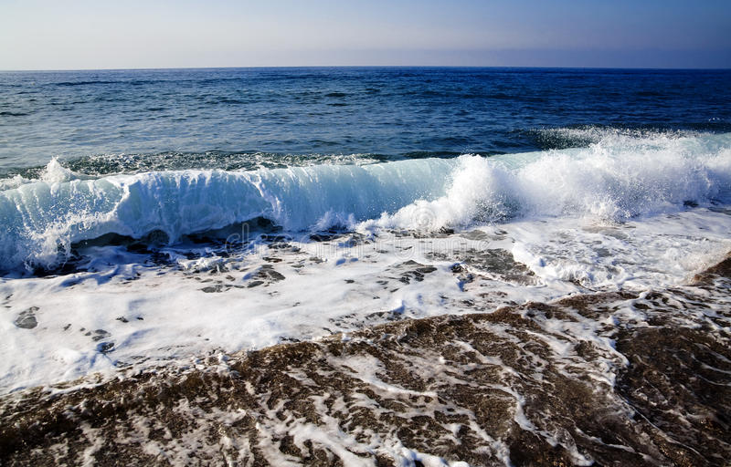 Foamy waves. Foamy shore blue waves over the horizon in a clear summer day stock photos