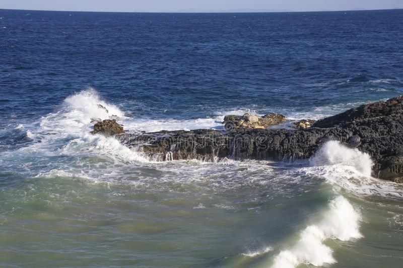 Foamy waves crashing against a stone cliff at high tide. stock images