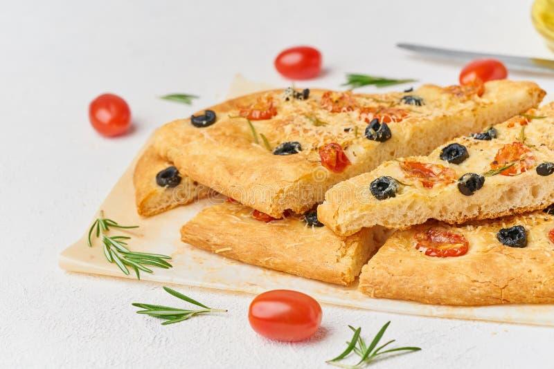 Focacce, pizza, pain plat italien coupé en tranches avec des tomates, olives et romarin Vue de c?t?, l'espace de copie photos libres de droits