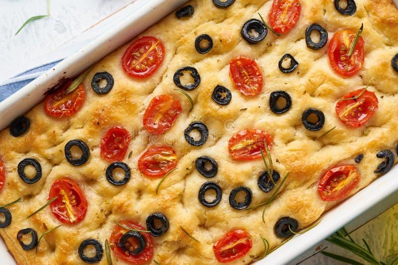 Focaccia用蕃茄、橄榄和迷迭香在砂锅,顶视图,宏指令 传统意大利平的面包 免版税库存图片