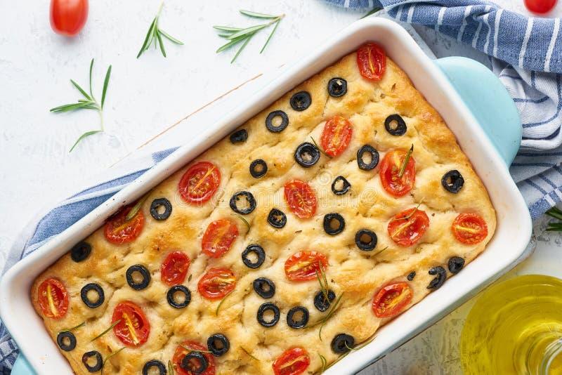 Focaccia用蕃茄、橄榄和迷迭香在砂锅,顶视图 传统意大利平的面包 免版税库存图片