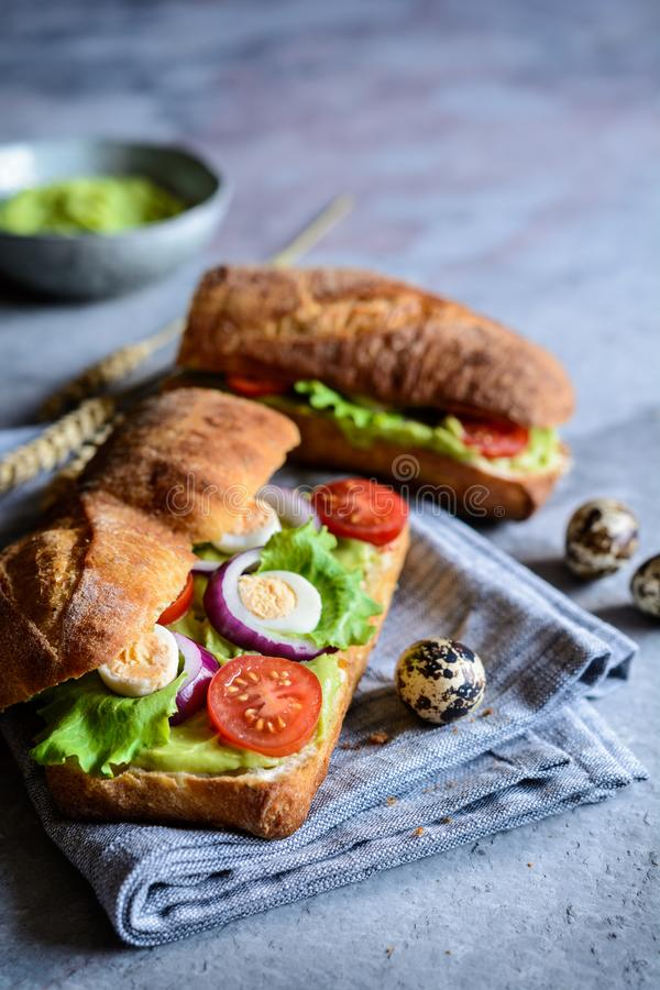 Focaccia baguette with avocado spread, lettuce, tomato, onion and quail eggs royalty free stock photo