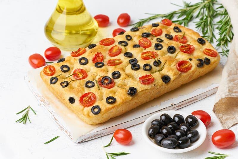 Focaccia com tomates, azeitonas e alecrins Pão liso italiano inteiro, garrafa com óleo imagens de stock royalty free