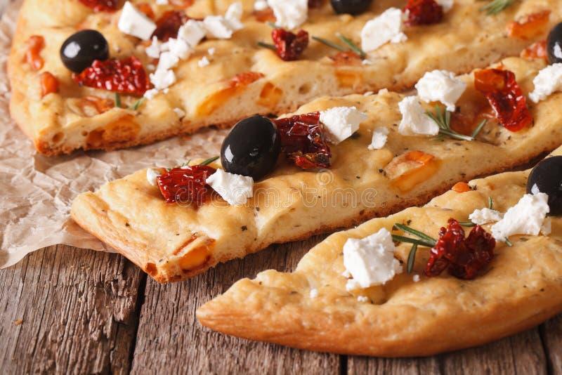 Focaccia cortado com tomates, feta e azeitonas secados hori macro imagem de stock royalty free